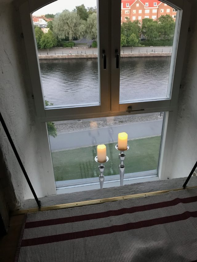 Attic Window With Cozy Lit Candles Overlooking River