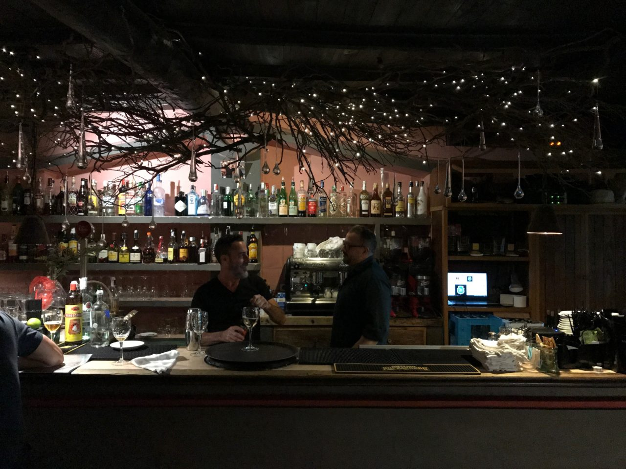 Bartenders Talking In A Bar With Bottles And Glasses