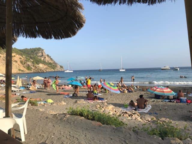 People Sun Bathing On A Beach With Umbrellas
