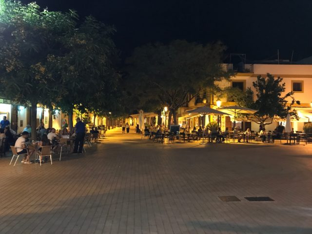 A Square With Cafés, People And Trees At Night
