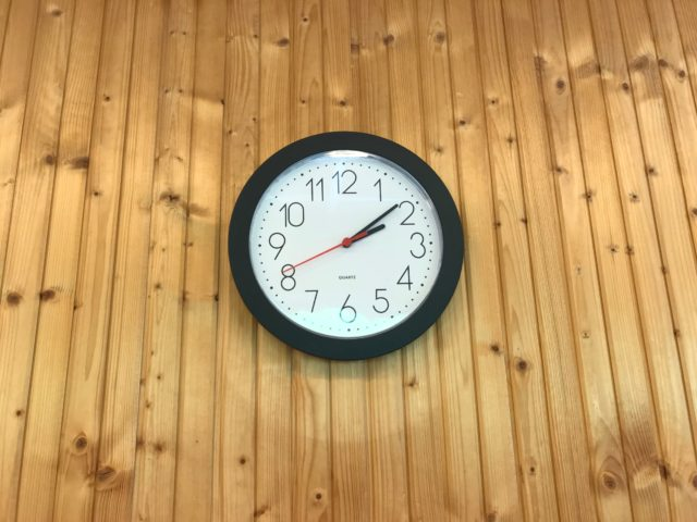 Clock On Wood Panel Wall Showing The Current Time