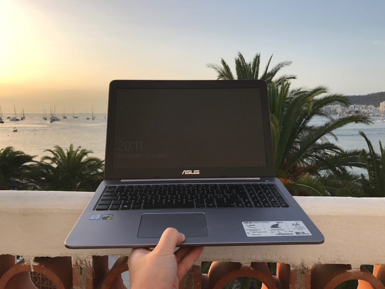 Hand Holding Laptop In Front Of Tropical Ocean