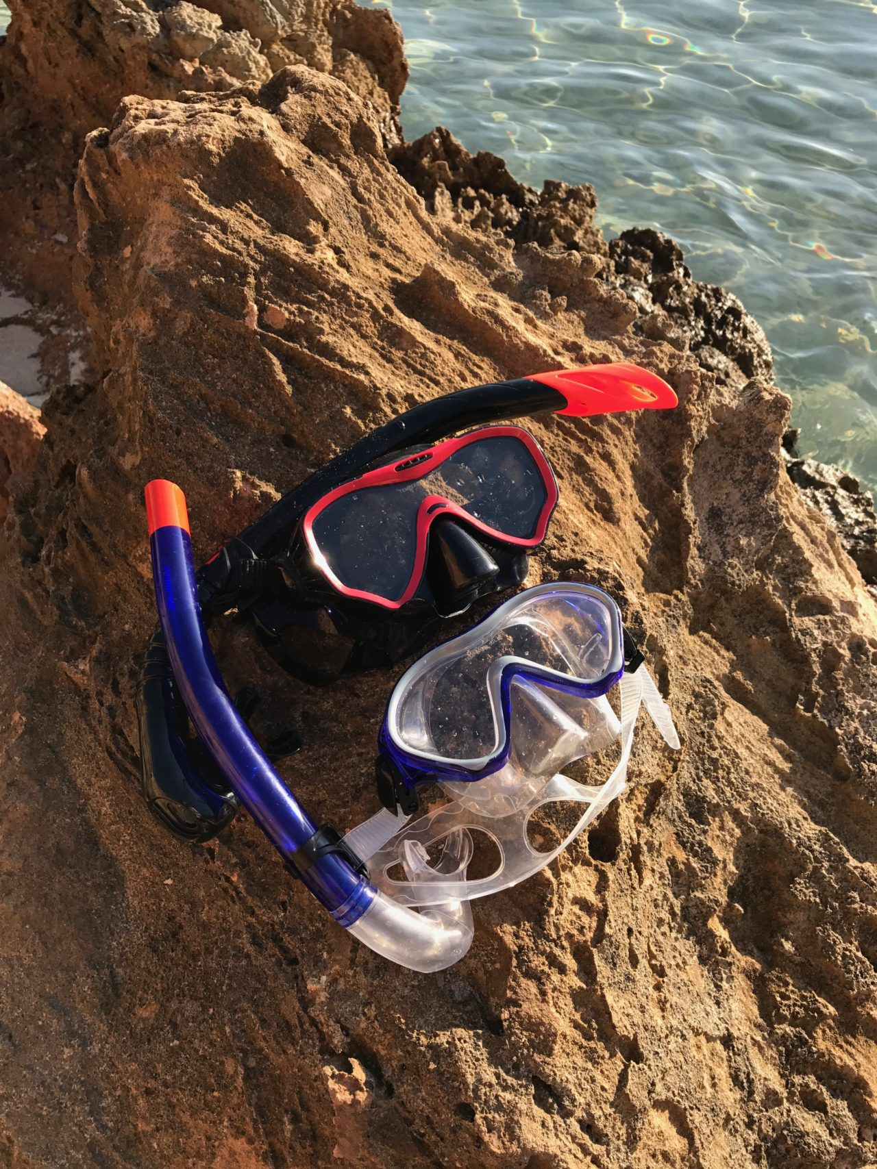 Two Sets Of Diving Goggles And Gear On Rock By Ocean