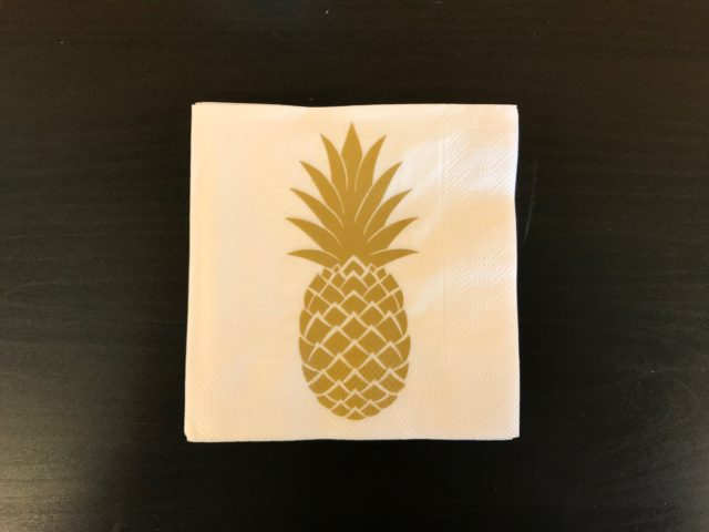Golden Pineapple Party Napkin On A Black Table