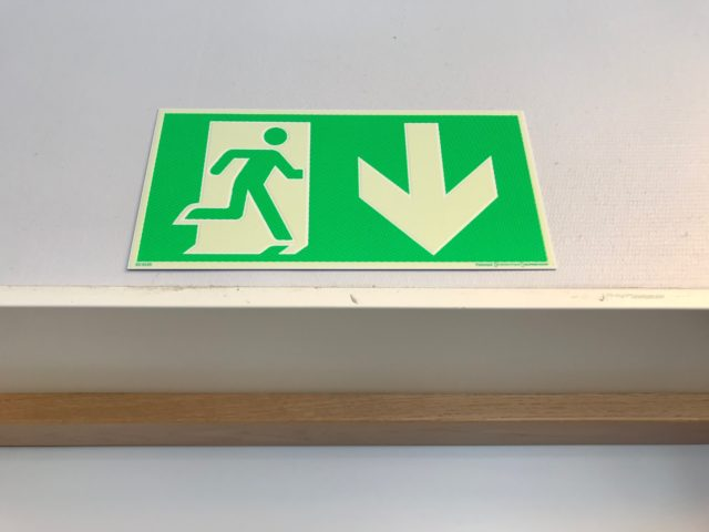 Green Emergency Exit Sign Over A Door