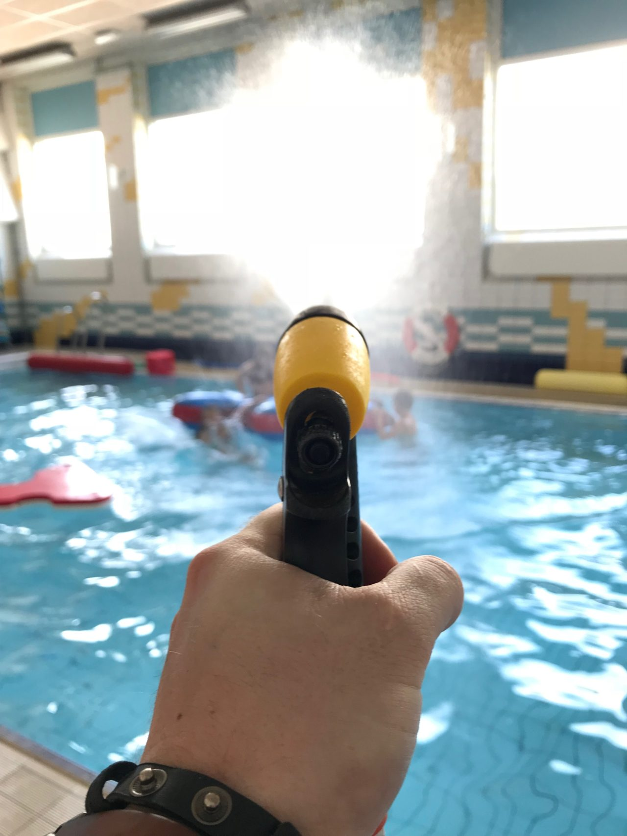 Hand Holding Water Gun Spraying Swimmers In Pool
