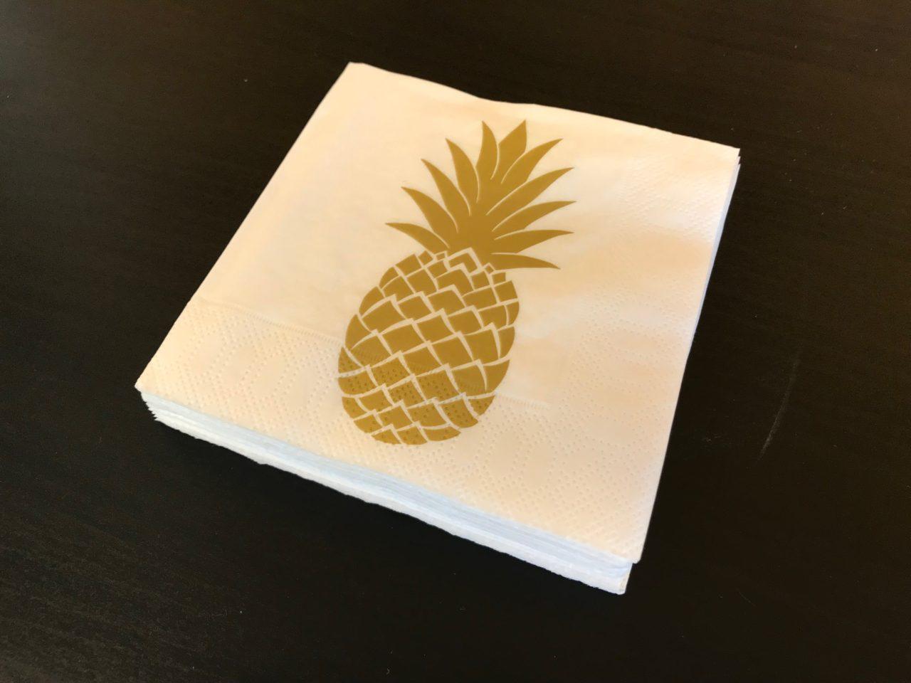 Golden Pineapple Napkin On A Black Table