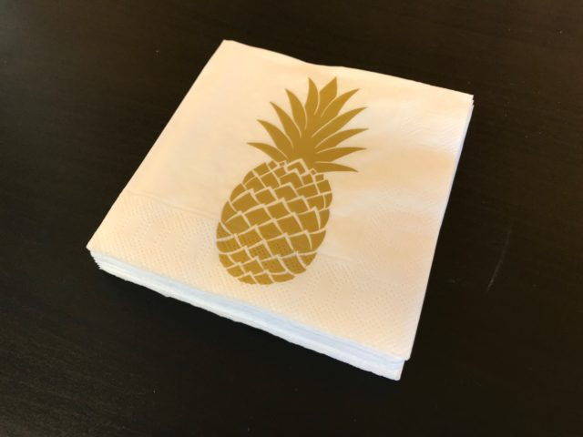 Golden Pineapple Napkin On A Black Table