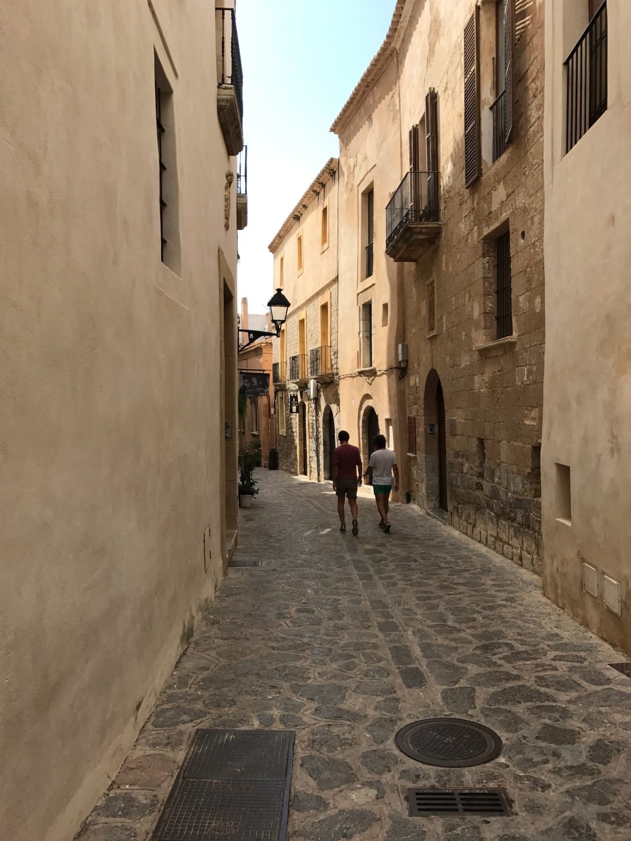 Narrow Street With Doors And Windows And People Walking On Cobblestone