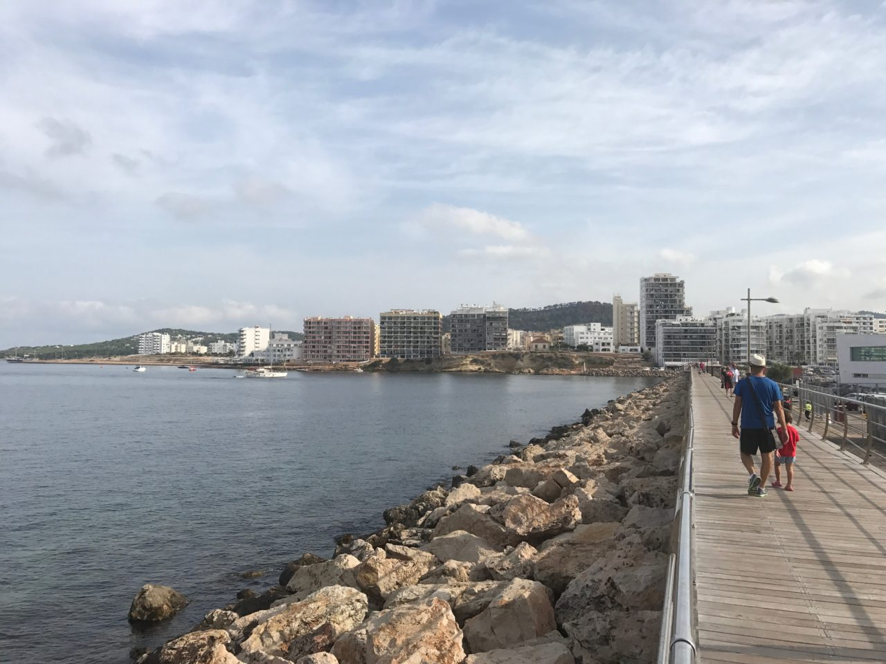 People Walking On A Pier With City View