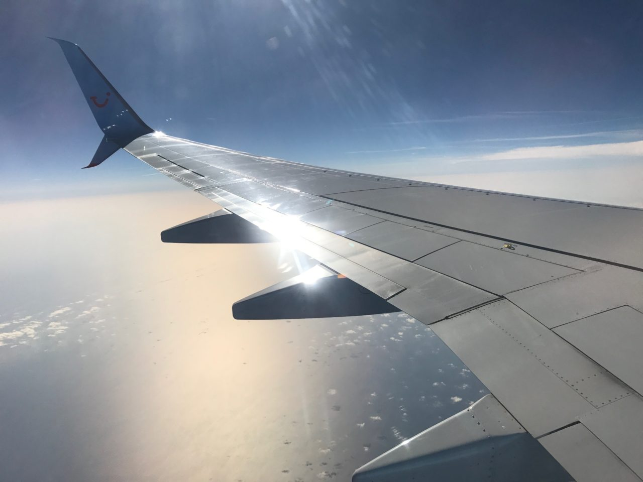Plane Window View Of Wing Over Sea With Clouds