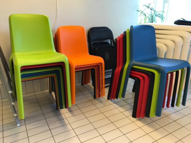Colorful Plastic Chairs Stacked On A Tile Floor