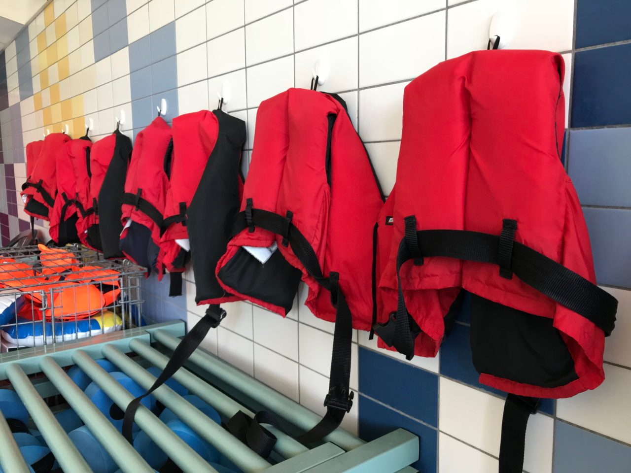 Lined Up Red Lifevests For Swimming On Wall Hangers