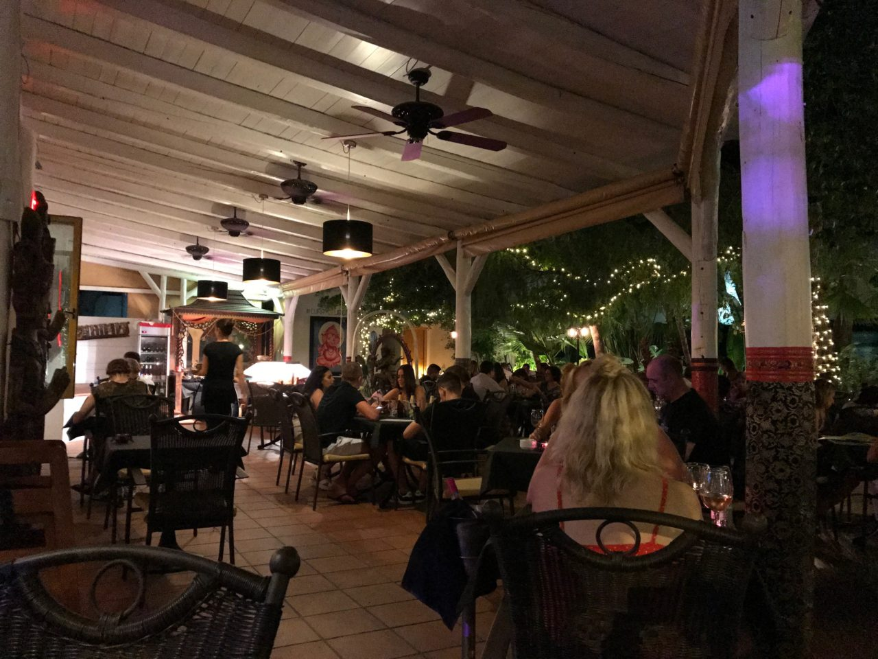 People Sitting In A Restaurant Eating With Fans And Lights
