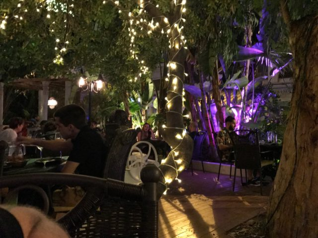 People Aitting Food At Tables Eating In A Restaurant With Lights