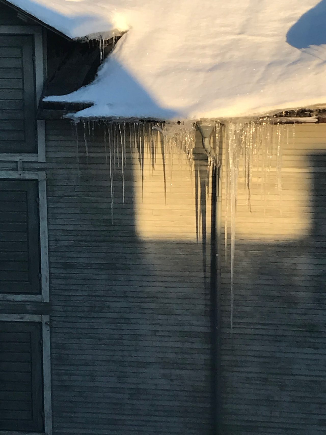 Roof With Snow And Icicles Hanging Down From The Gutter