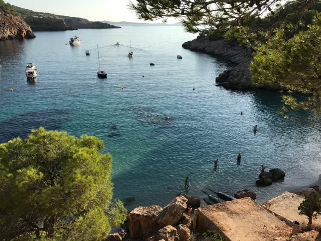 Tropical Cove With Swimmers And Boats In The Ocean