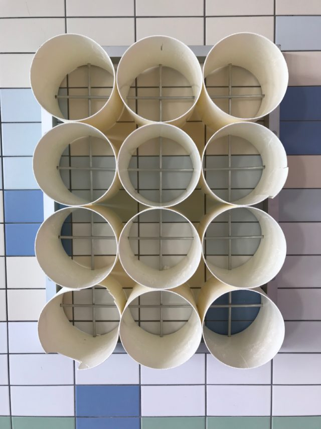 Storage Pipes Mounted On Tiled Wall