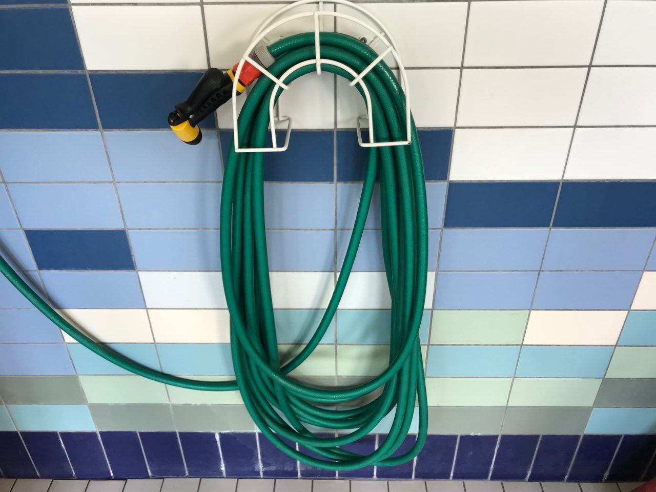 Rolled Up Water Hose Mounted On Wall Holder
