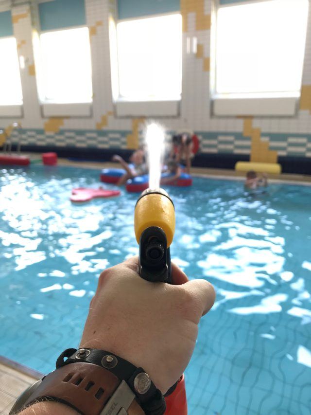 Water Hose Gun Sparying Water Into Pool With Kids And Toys