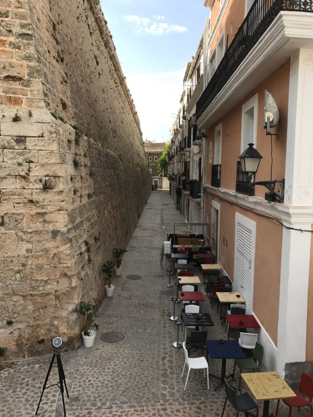 Narrow Street Restaurant With Tables And Chairs