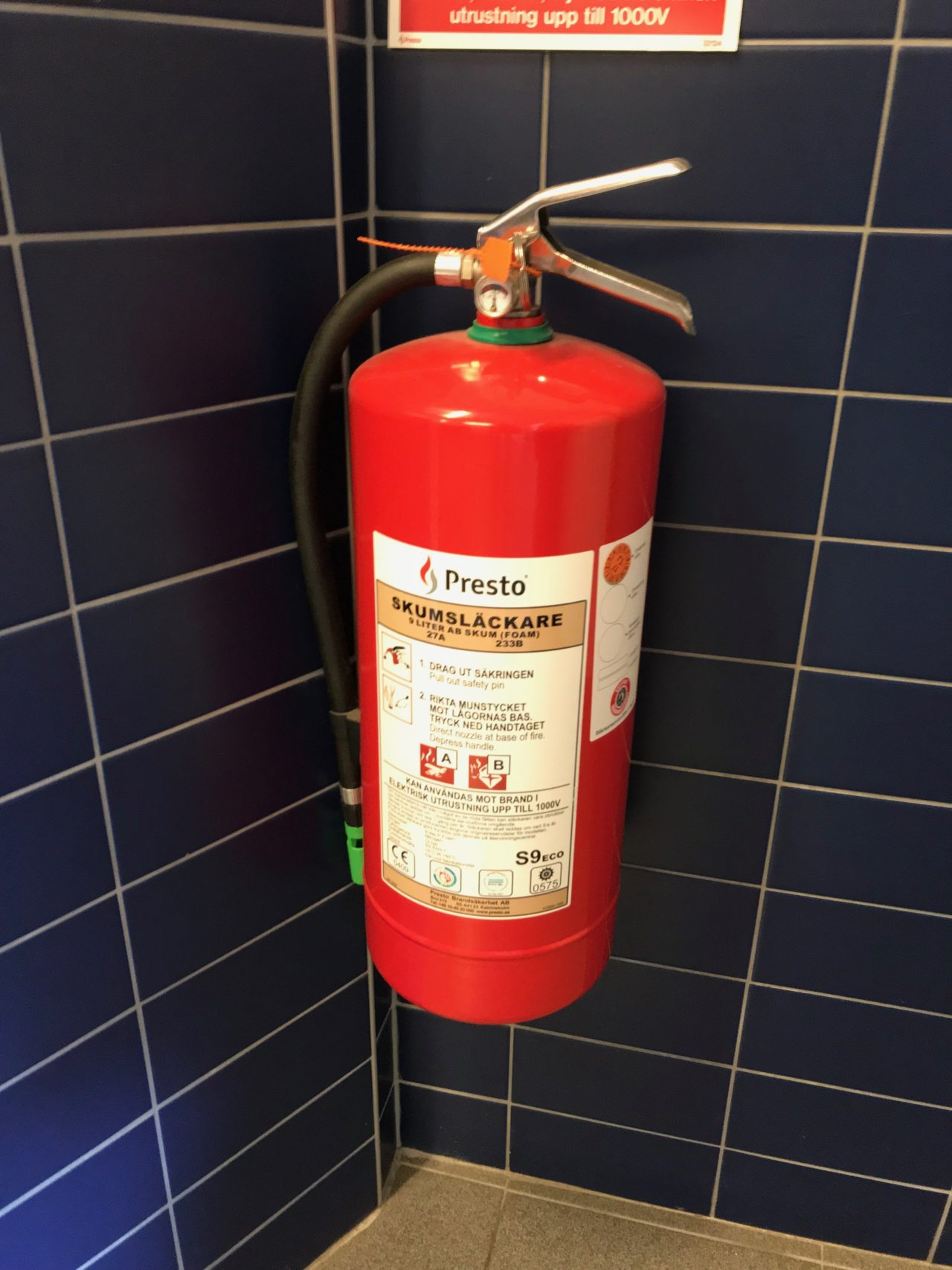Red Fire Extinguisher Hanging On Tiled Wall