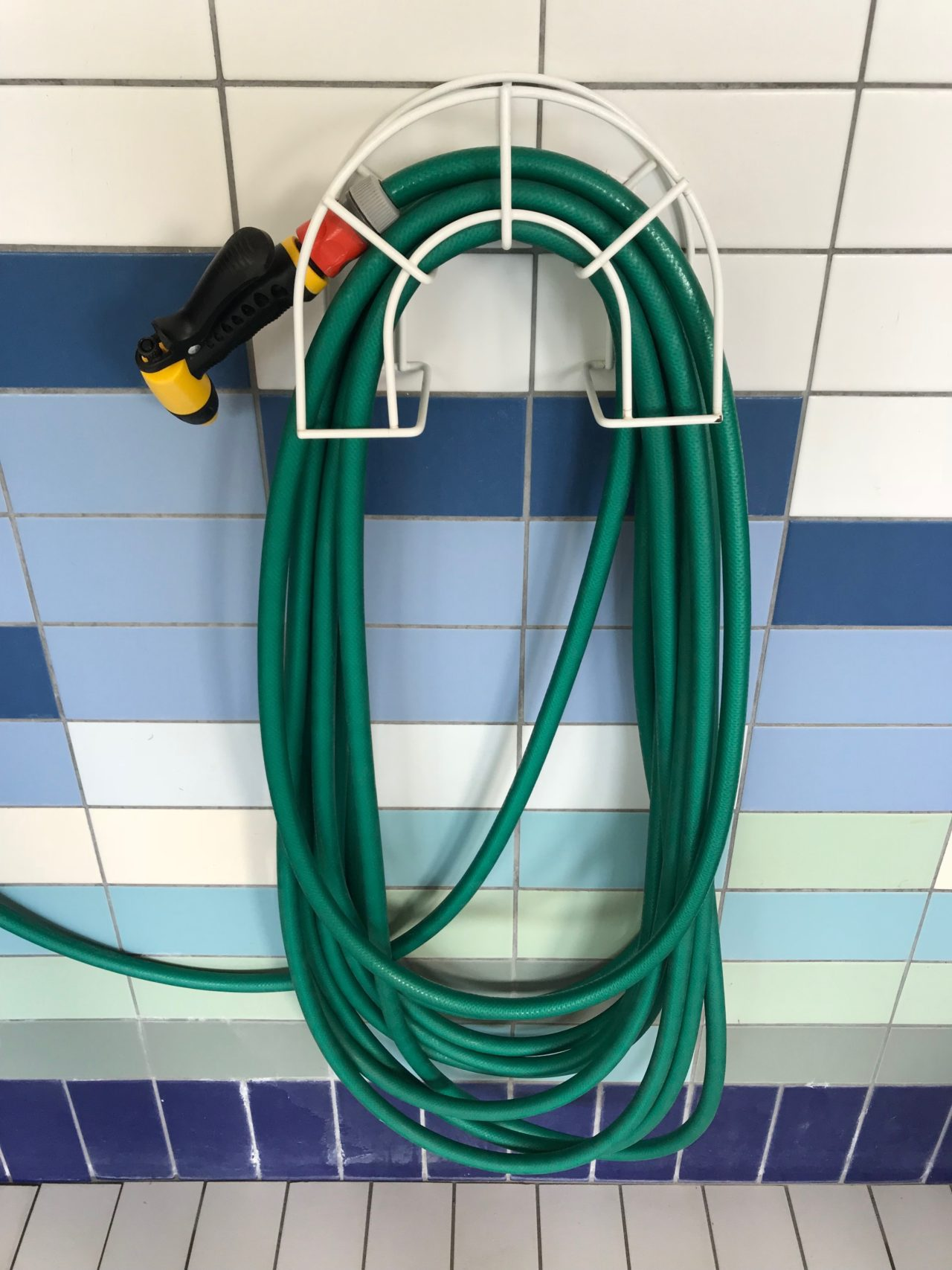 Rolled Up Green Water Hose Hanging On Tiled Wall
