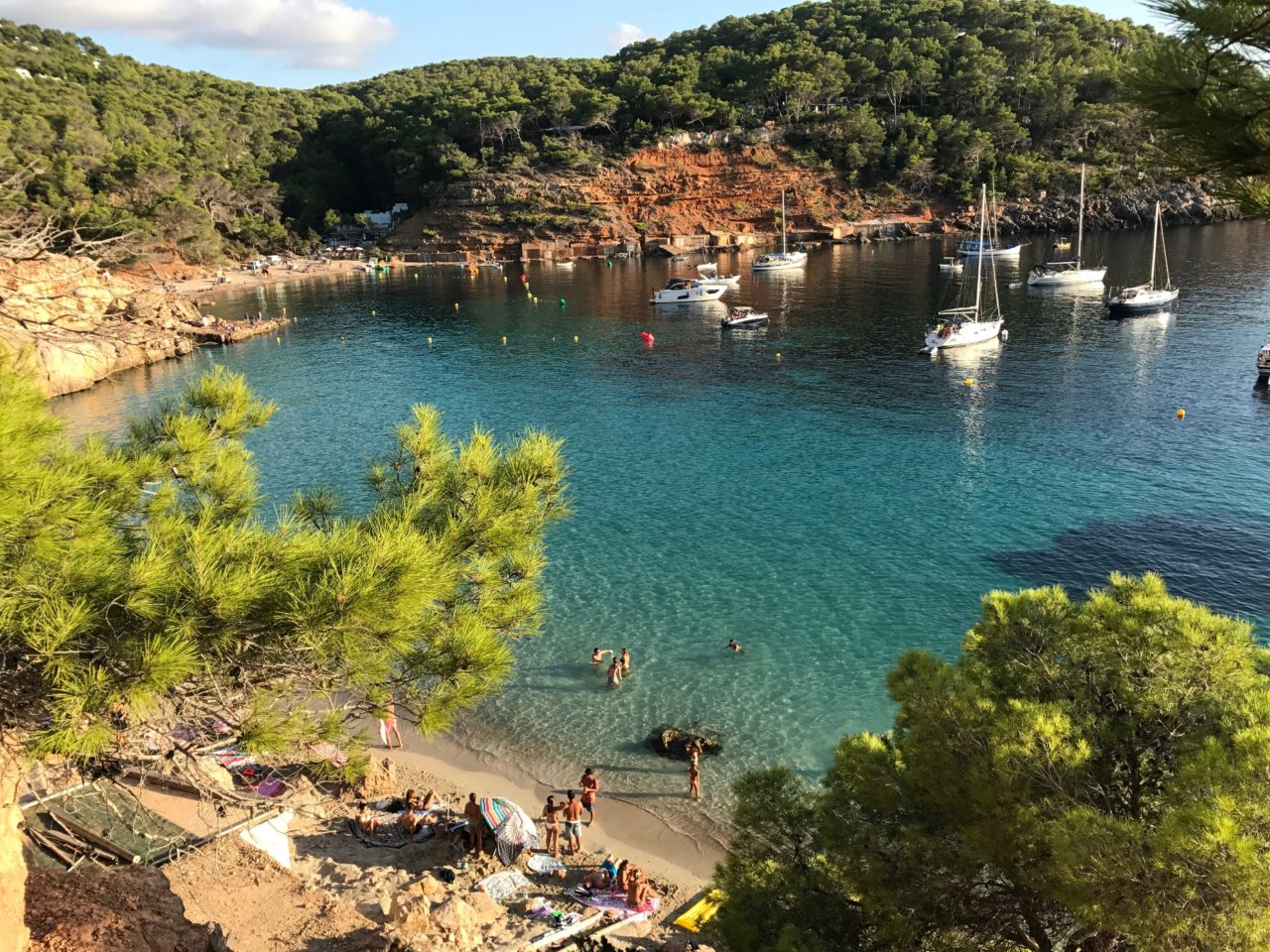 Tropical Beach In The Afternoon With Boats And Swimmers