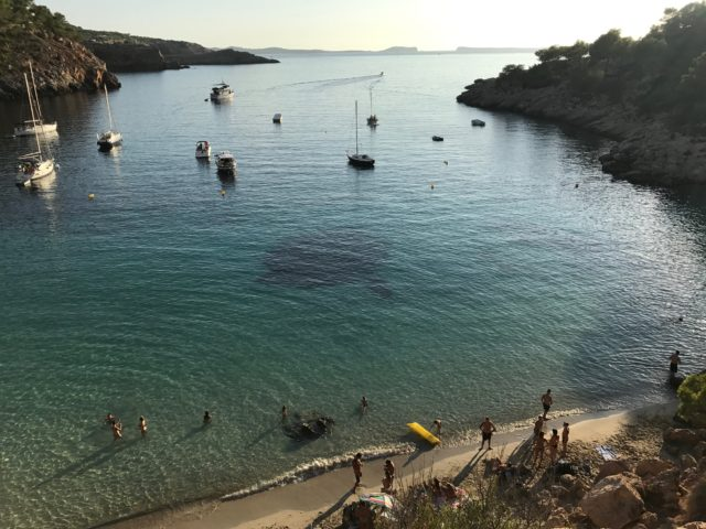 Beach Sunbathers And Boats Anchored In Cove At Sunset
