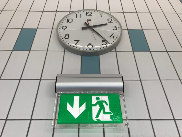 Clock On Tiled Wall With Emergency Sign Underneath It