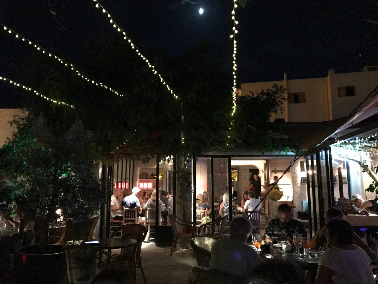 Outside Restaurant With Tables And Guests Under Cozy Lights