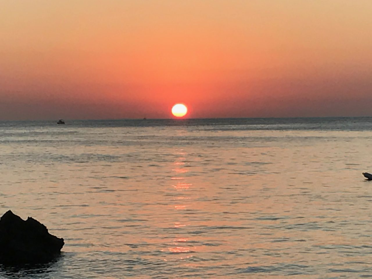 Sun Setting In The Ocean With Boat And Cliff