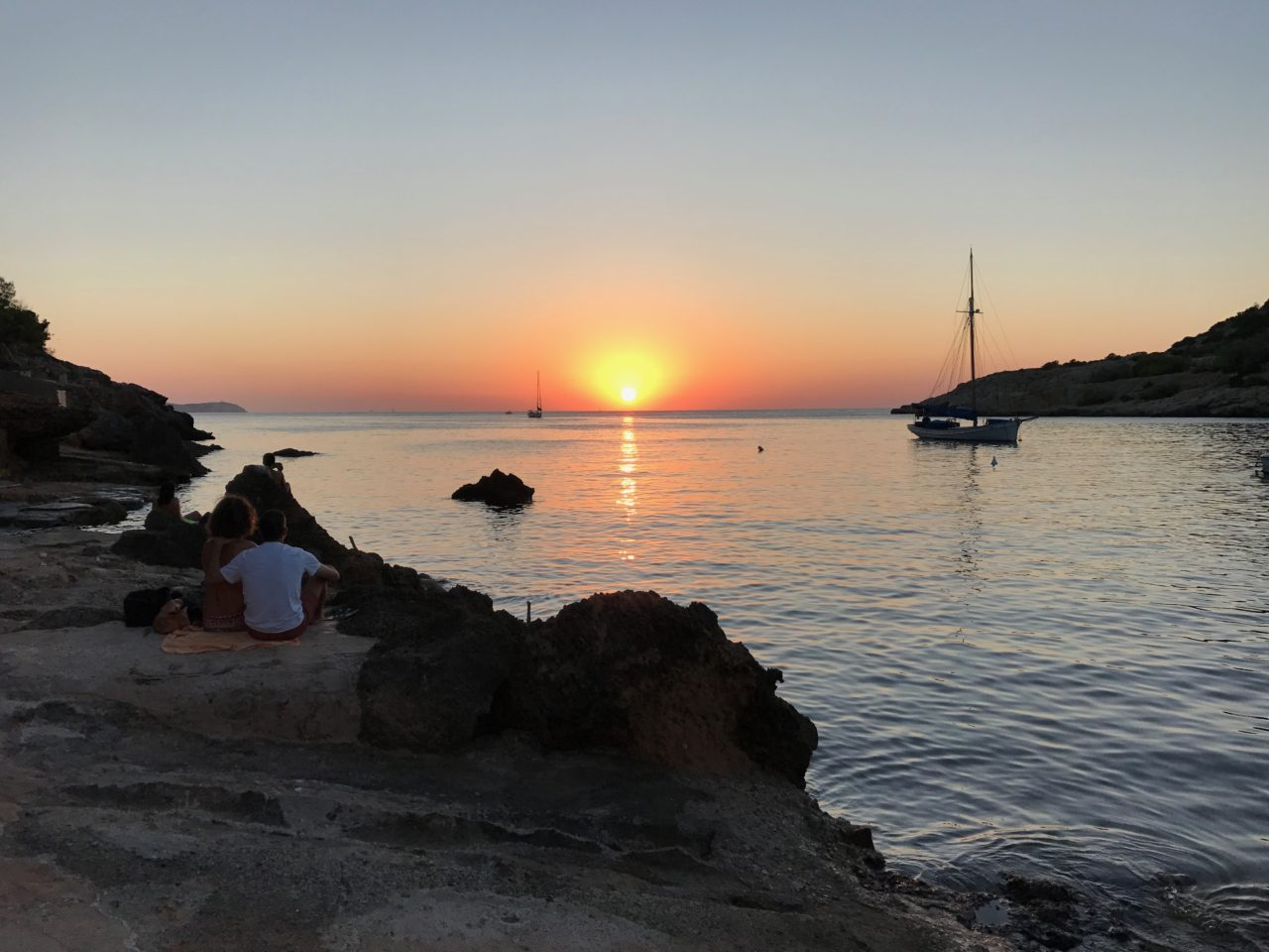 Ocean Sunset With People And Sail Boat