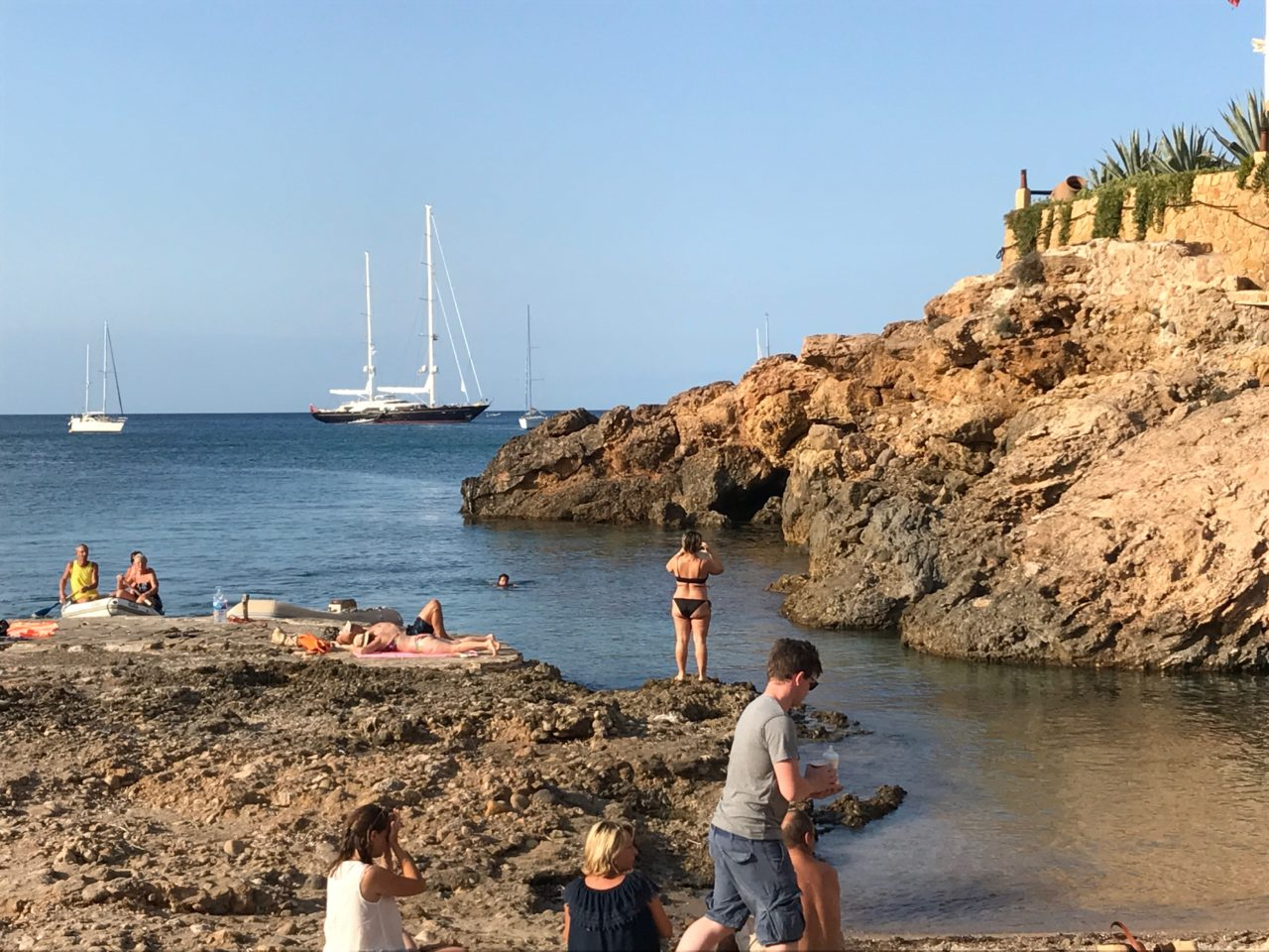 Sunbathers On Cliff With Sail Boats In The Background