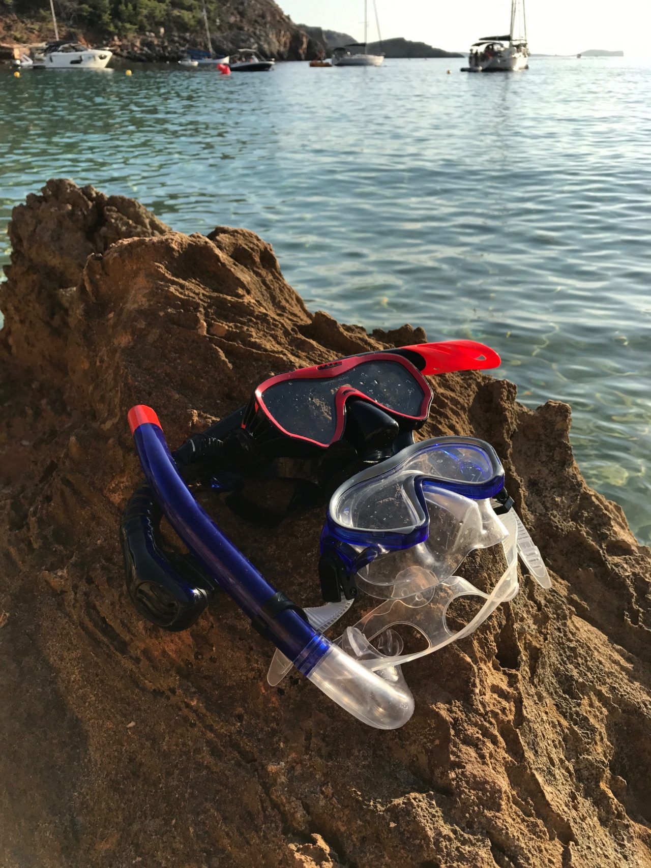 Snorkeling Gear On A Cliff By The Ocean With Boats