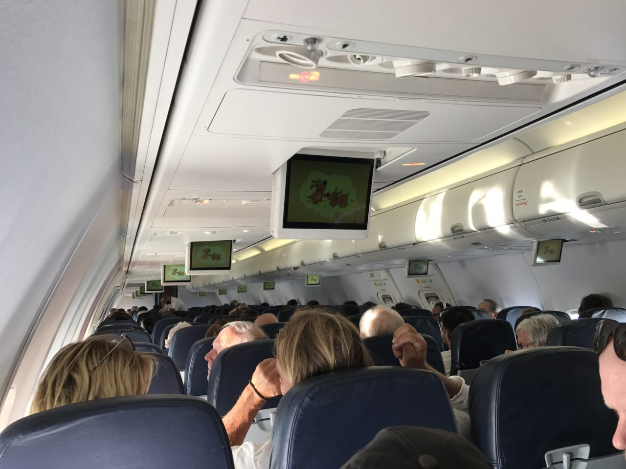 Inside Airplane Cabin With People Sitting Down
