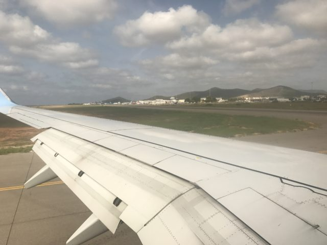View Of Airplane Wing On Runway With Cloudy Sky