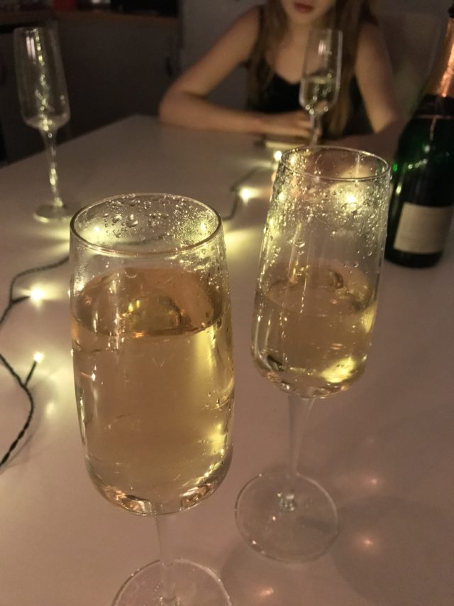 Glasses And Bottle Of Champagne With Table Lights