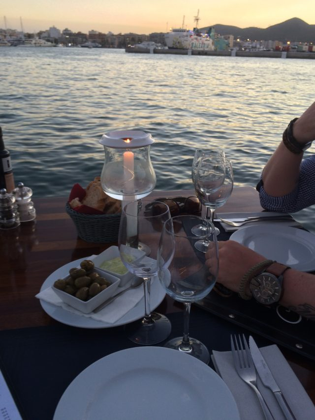 Romantic Dinner By The Sea With Candles And Olives And Aioli And Bread On Brown Table