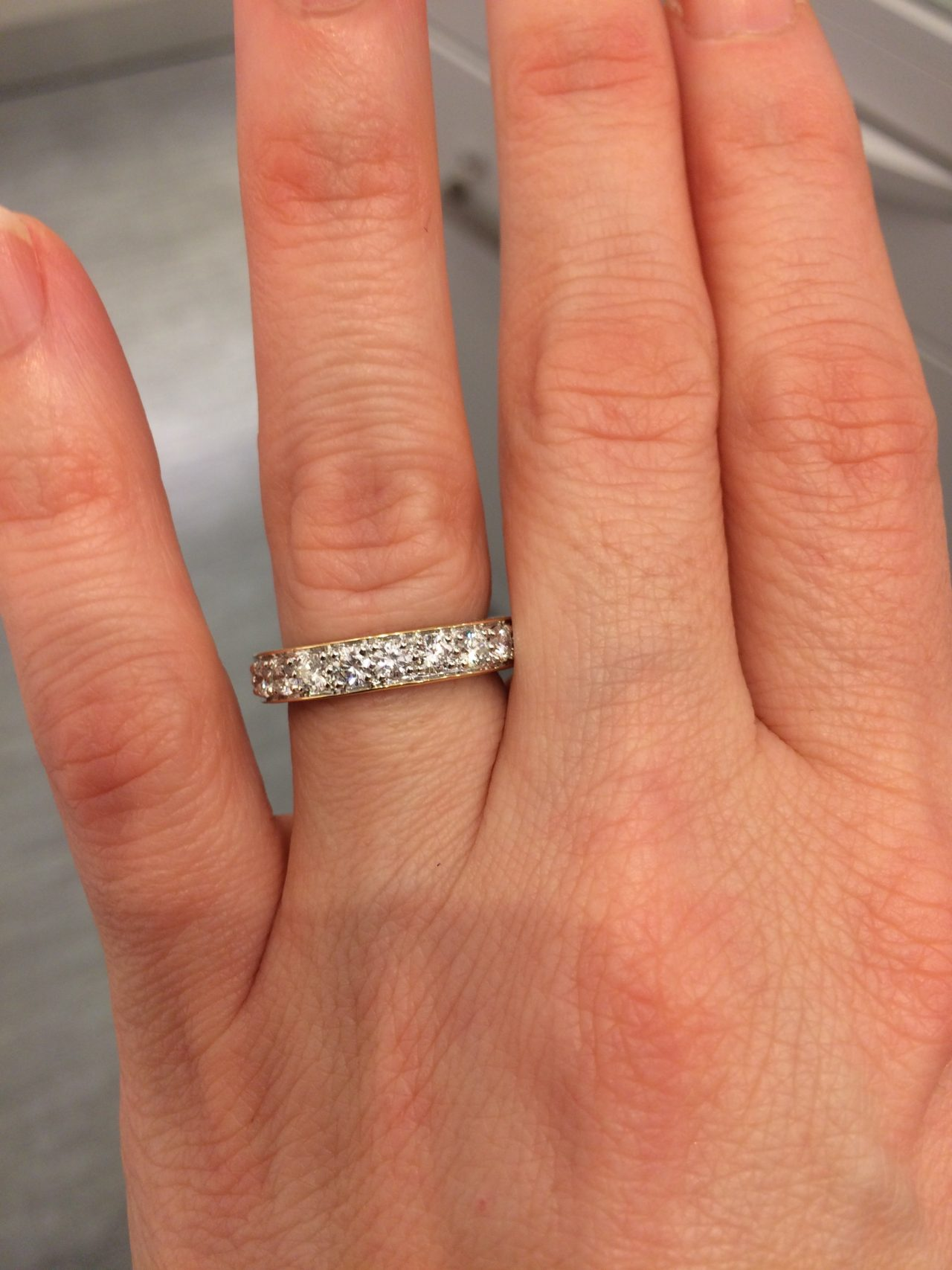 Hand With A Beautiful White Gold Ring With Small Diamonds Against A Light Gray Background