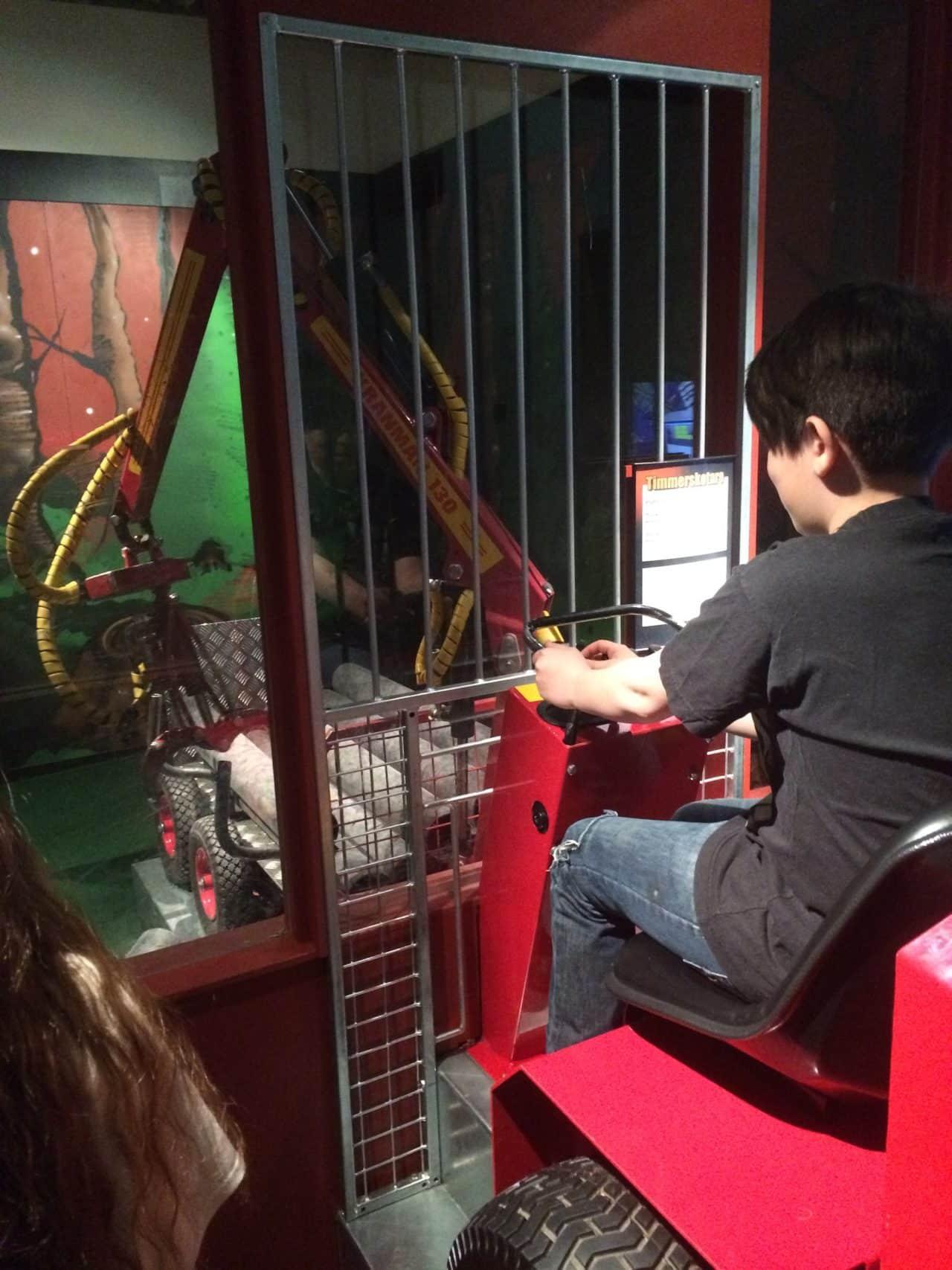 Boy Runs A Mini Machine Lifting Logs In A Technological Museum In Sweden