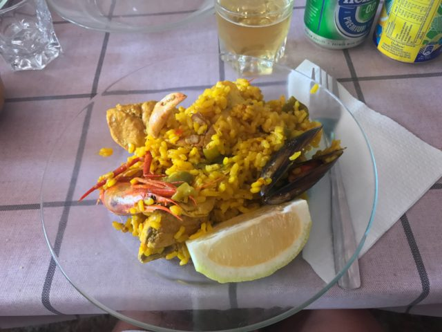 Glass Plate Of Paella With Shrimp And A Lemon