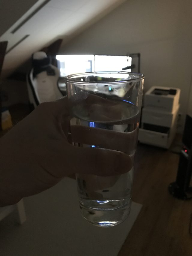 Holding A Glass Of Water In An Office Room