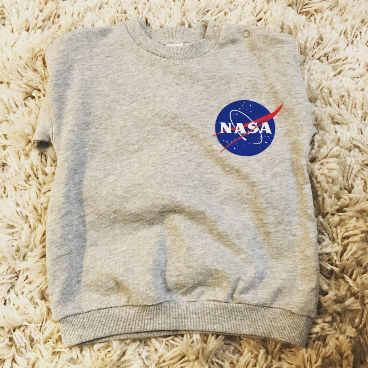 Gray Kid's NASA Sweater Laying On A Rug