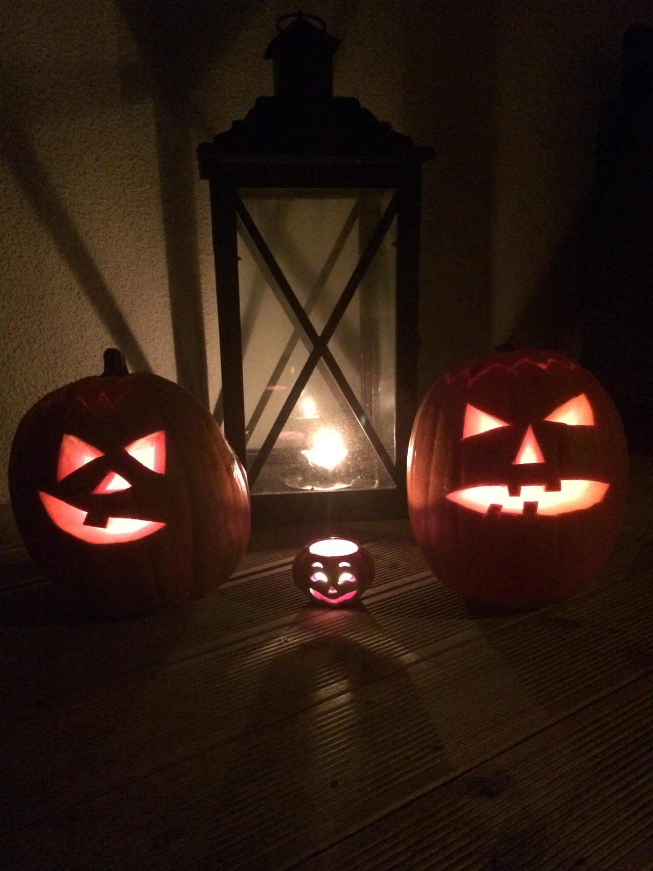 Scary Pumpkins And A Little Cute Pumpkin In The Dark On Halloween With Lighted Tealights In