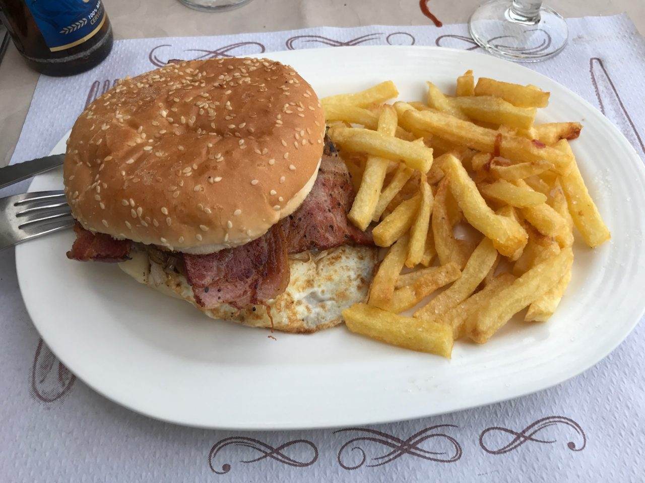 A Hamburger Of Beef With Bacon Slices And Fried Eggs And Salted French Fries On A White Plate