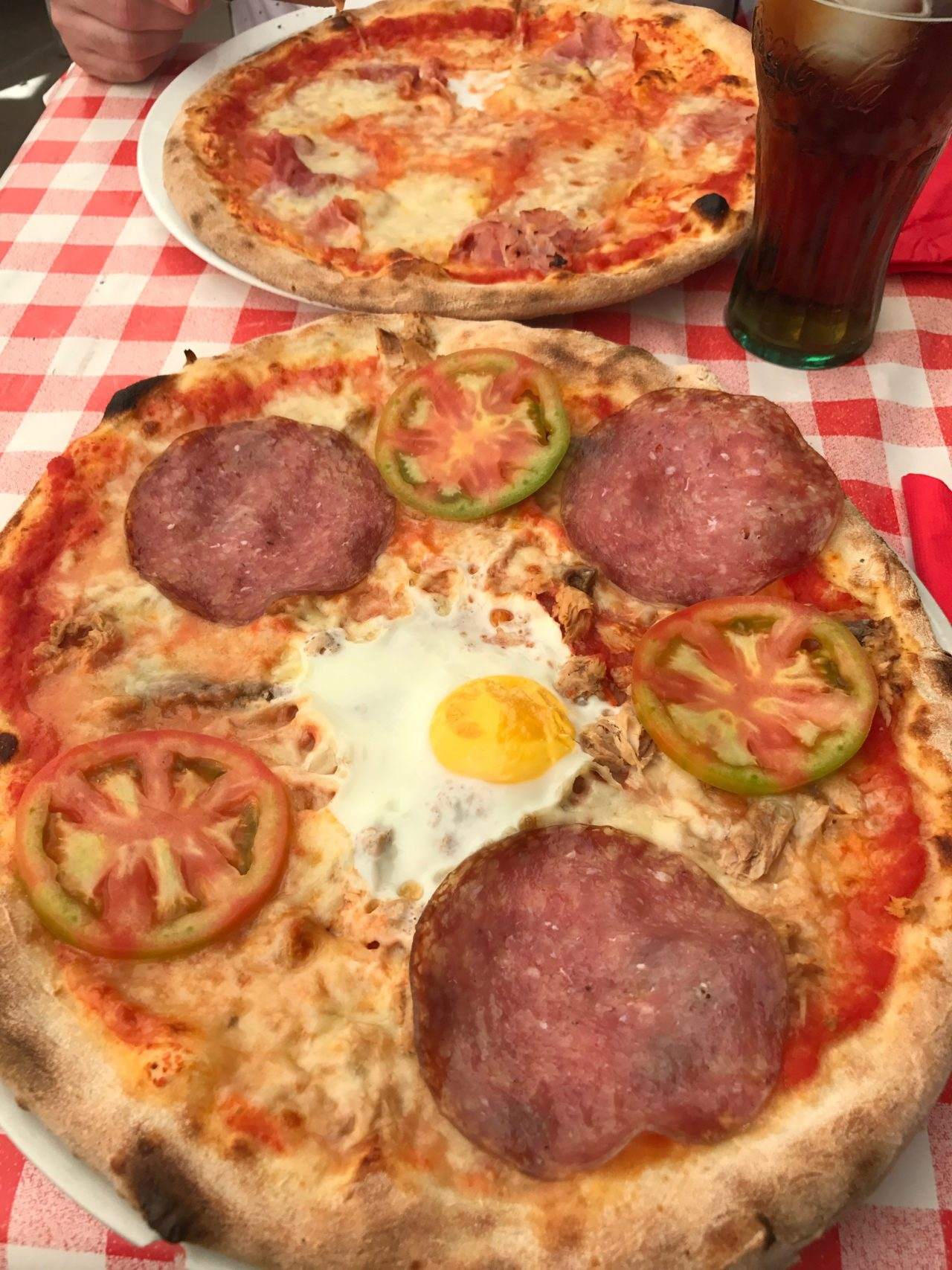 Pizzas With Salami And Eggs And Mozzarella On A Checkered Tablecloth With Drink