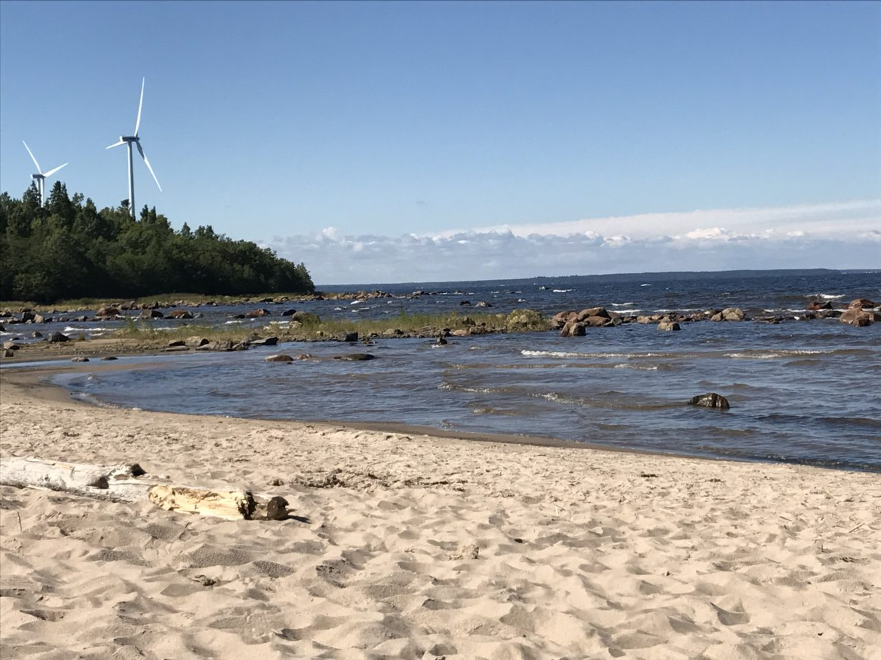 Sand And Rocks On Beach With Two Windmills In The Background