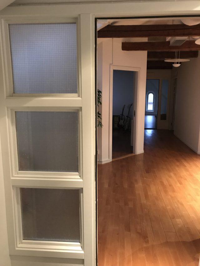 Open Door To Dark Hallway With Wooden Beams In Ceiling