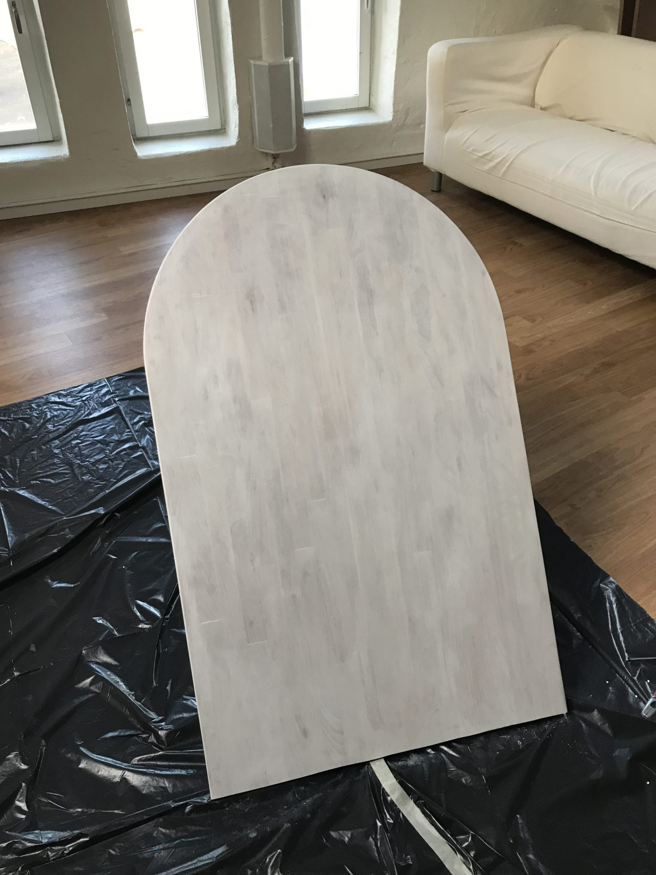 Bar Table Being Painted With Plastic Protection And A Couch In The Background